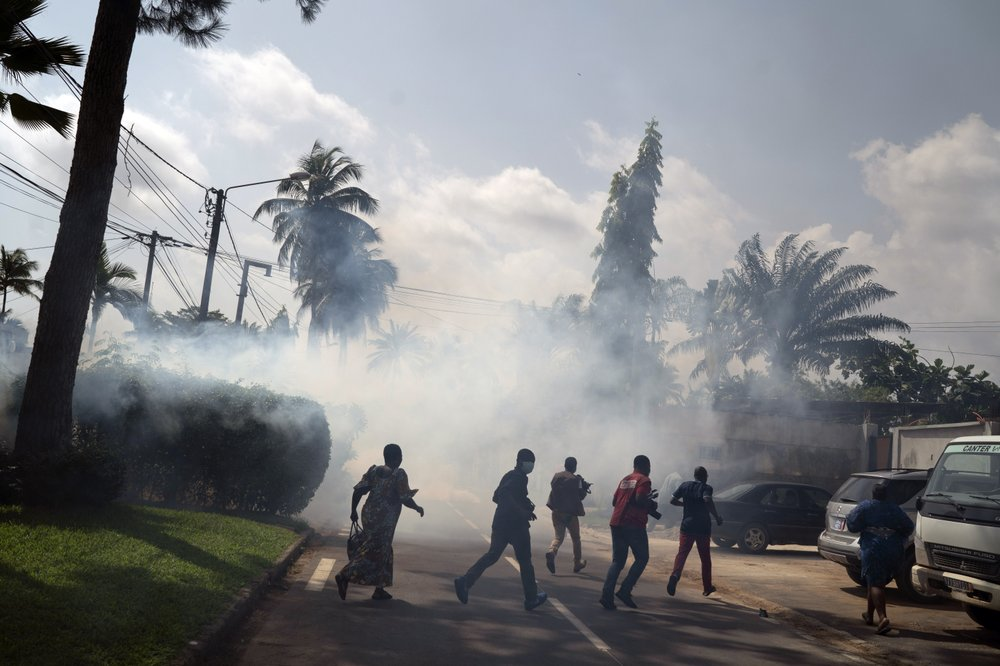 Supporters of the opposition parties and journalists run away from tear gas thrown by the riot police blocking access to the house of the former president Henri Konan Bedie, in Abidjan, Ivory Coast, Tuesday, Nov. 3, 2020. Ivory Coast's electoral commission said Tuesday that President Alassane Ouattara had overwhelmingly won a third term in office after his two main opponents boycotted the election and called his candidacy illegal. (AP Photo/Leo Correa)